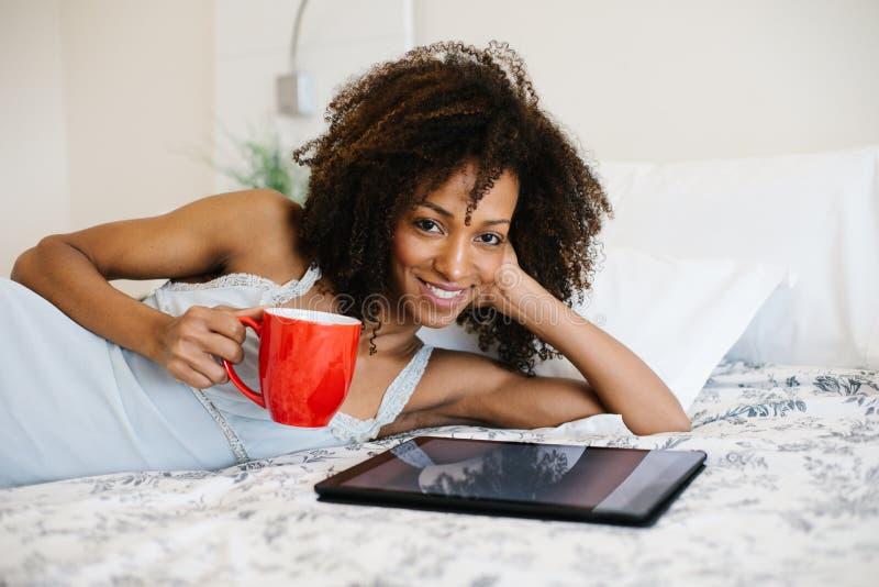 Mulher em casa que lê na tabuleta digital imagens de stock