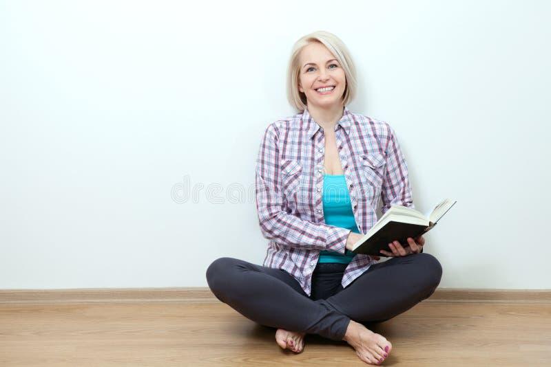 Mulher em casa que senta-se no livro do relaxamento e de leitura do assoalho imagens de stock royalty free