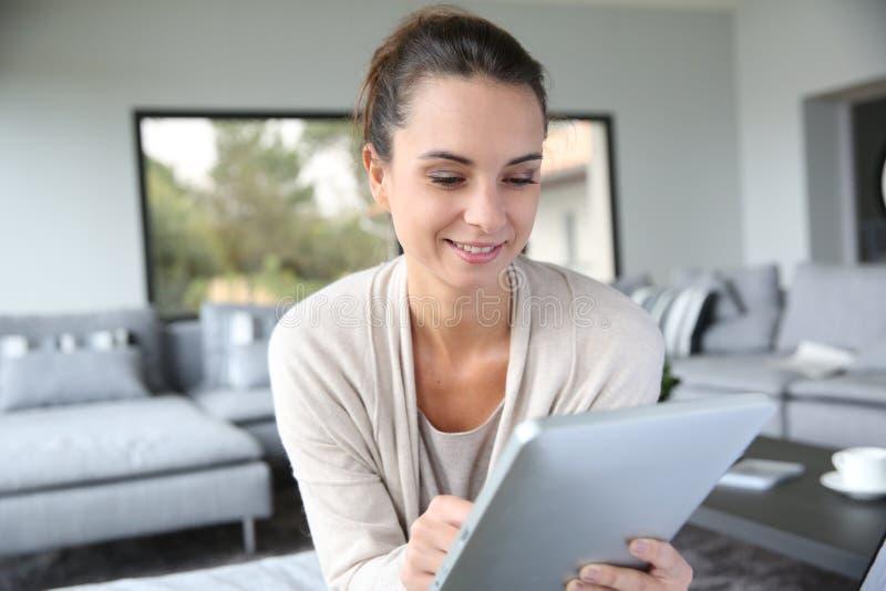 Mulher em casa que websurfing na tabuleta foto de stock royalty free