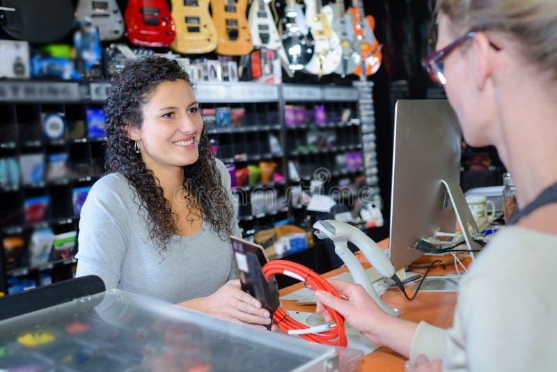 A mulher em checkout na loja da m?sica fotografia de stock royalty free