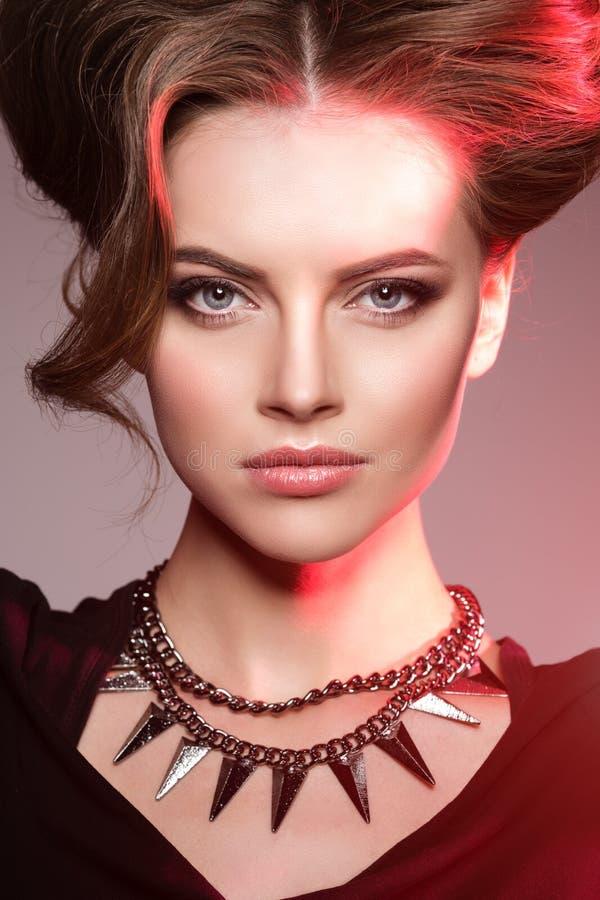 Mulher em Dia das Bruxas bruxa Menina com um olhar mau em uma luz vermelha fotografia de stock royalty free