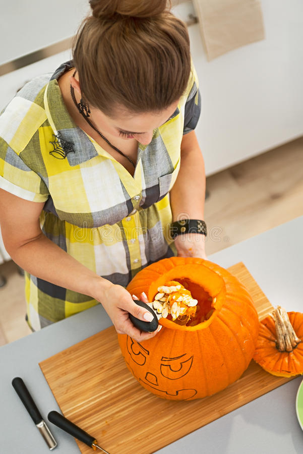 A mulher em Dia das Bruxas decorou a cozinha prepara a abóbora cinzelando fotografia de stock