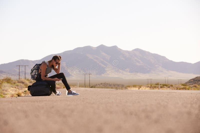 Mulher em férias que viaja ao longo da estrada usando o telefone celular fotos de stock royalty free