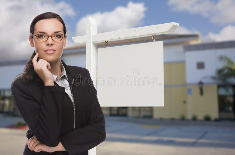 Mulher em Front Commercial Building e no sinal vazio de Real Estate foto de stock