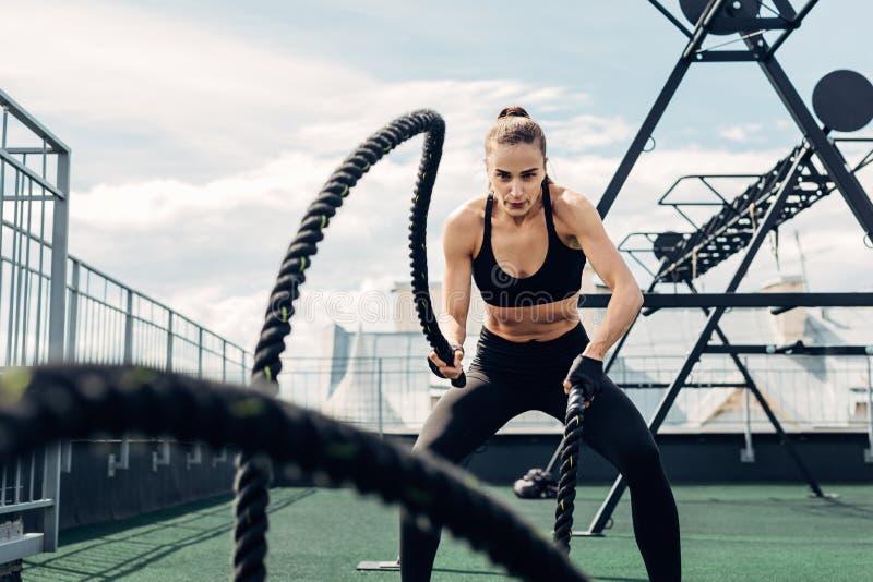 Mulher em ginástica desgasta trabalhando com duas cordas de batalha imagem de stock