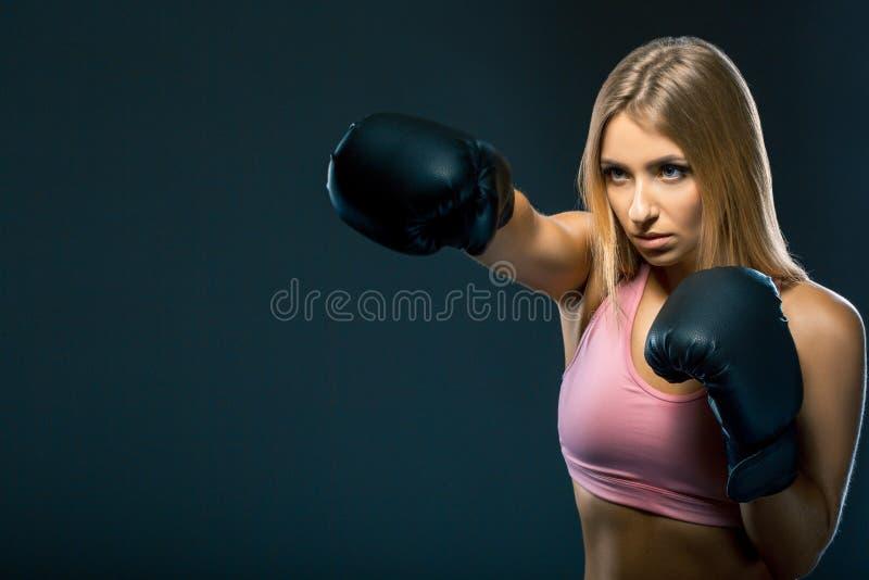 A mulher em luvas de encaixotamento e em sportswear golpeia no exercício no fundo escuro Copie o espaço imagem de stock royalty free