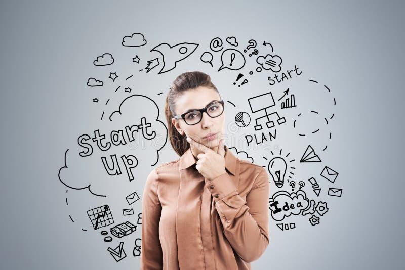 Mulher em marrom e em startup no cinza imagem de stock royalty free