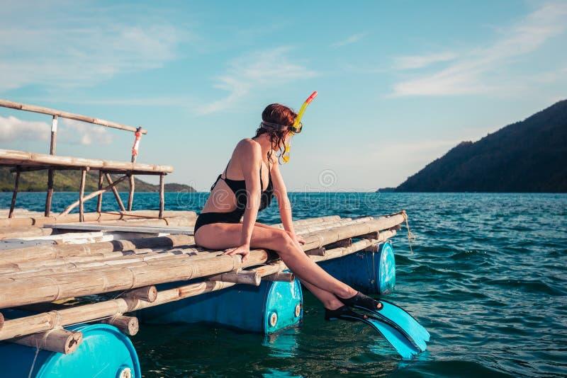 Mulher em mergulhar a engrenagem na jangada fotografia de stock royalty free