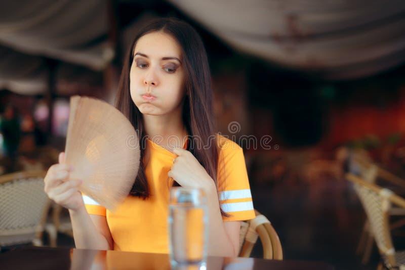 Mulher em ondas de um calor de combate do restaurante com um fã imagem de stock