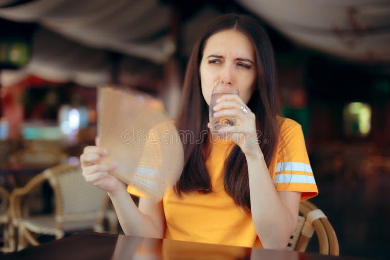 Mulher em ondas de um calor de combate do restaurante com um fã foto de stock royalty free