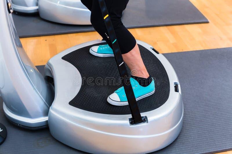 Mulher em placas de vibração no treinamento do gym fotografia de stock