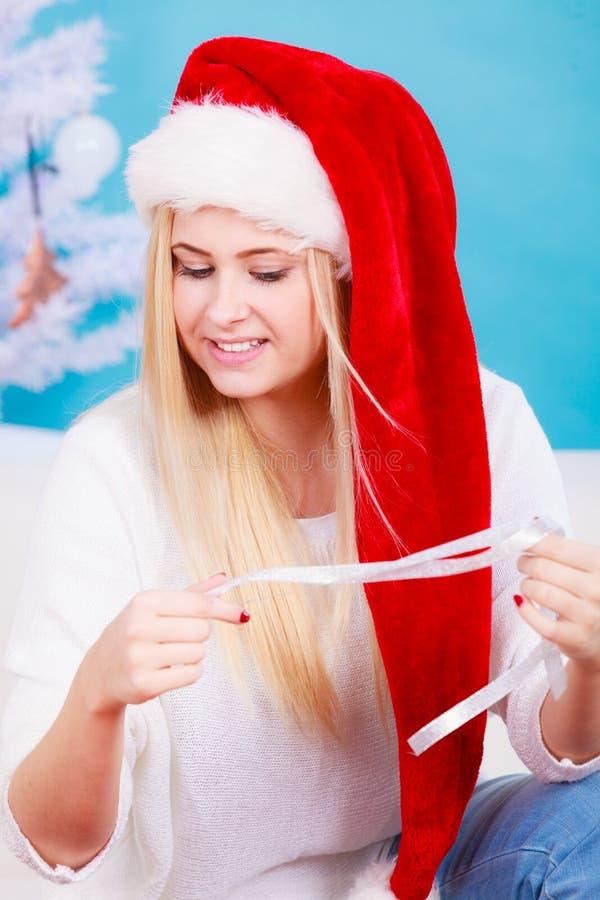 Mulher em presentes de Natal da abertura do chapéu de Santa fotos de stock royalty free