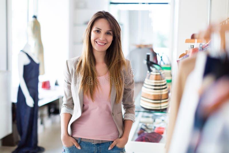 Mulher em seu boutique da roupa imagens de stock