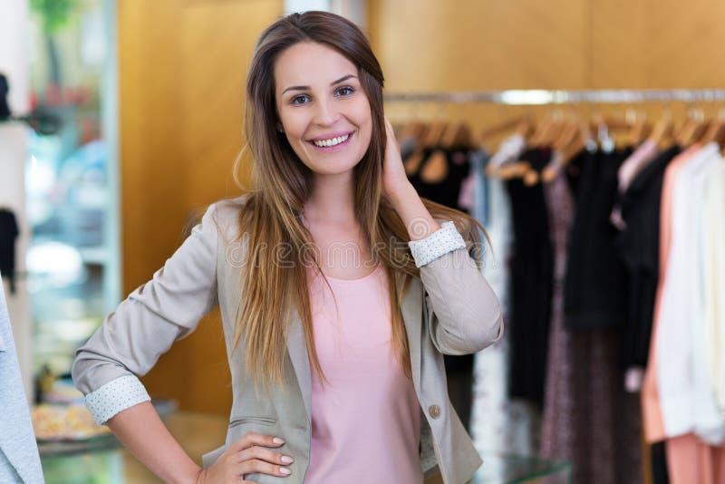 Mulher em seu boutique da roupa foto de stock