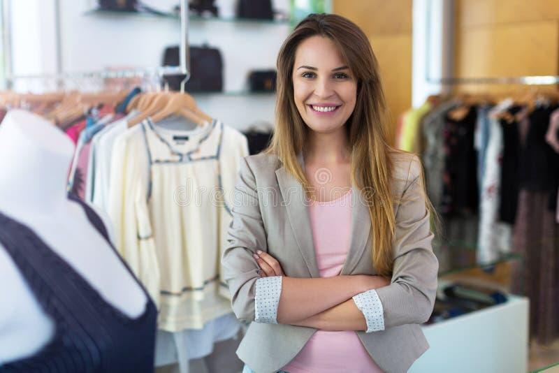 Mulher em seu boutique da roupa fotografia de stock