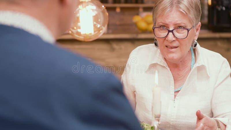 Mulher em seus anos sessenta que dizem a seu marido uma história interessante durante horas de comer em um restaurante fotos de stock