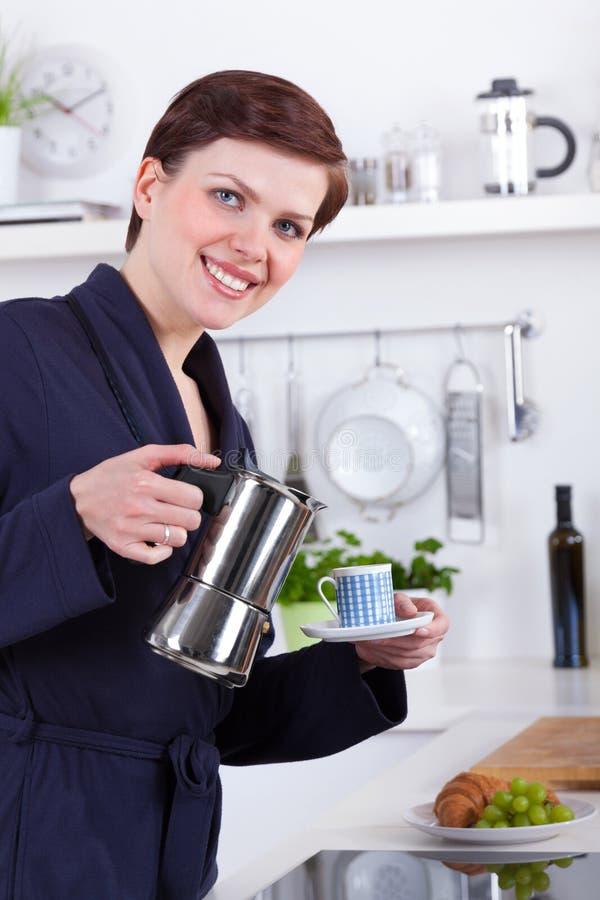 Mulher em sua cozinha que prepara o café com um potenciômetro do moka imagens de stock