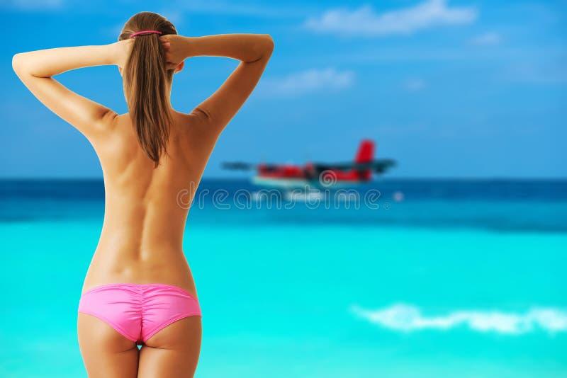 Mulher em topless na praia com o hidroavião em Maldivas fotografia de stock royalty free