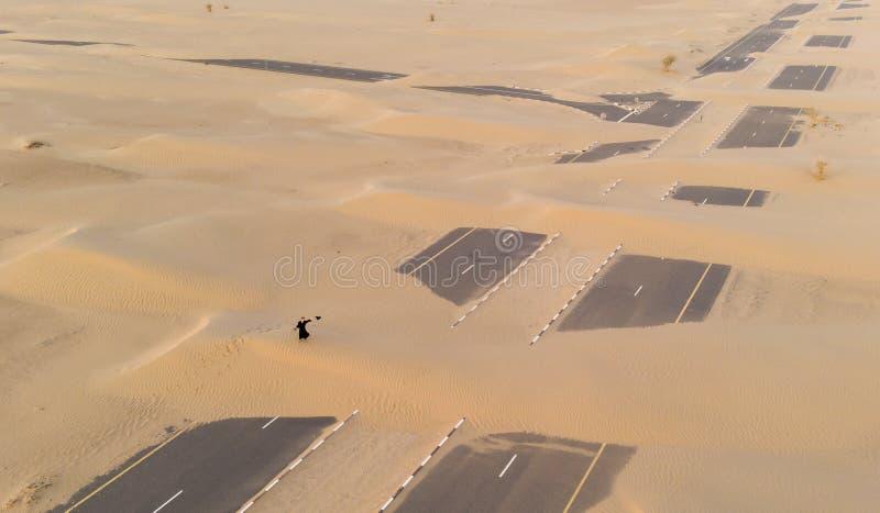 Mulher em um abaya em um deserto fotografia de stock