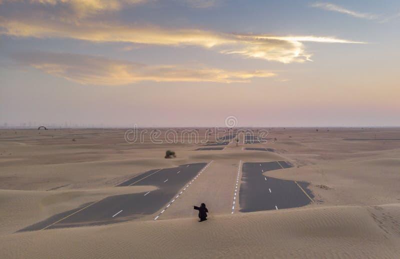Mulher em um abaya em um deserto imagem de stock royalty free