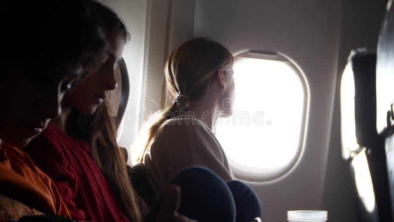 Mulher em um avião com crianças em um fundo da vigia imagens de stock royalty free
