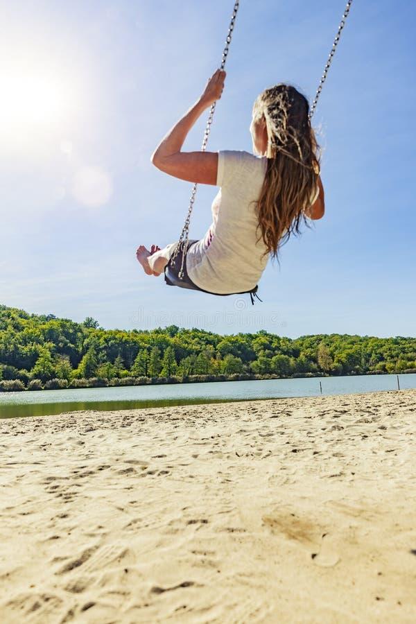 Mulher em um balanço em um lago fotografia de stock