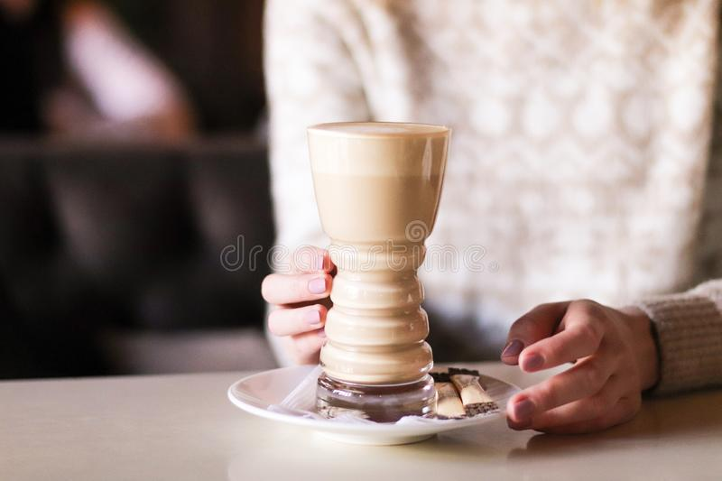Mulher em um bom humor para apreciar a xícara de café que senta-se no café imagens de stock