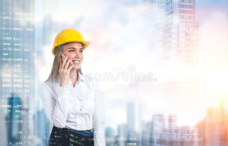 Mulher em um capacete de segurança em uma cidade imagens de stock royalty free