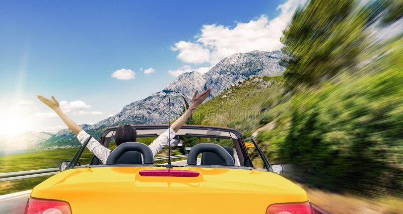 Mulher em um carro convertível na estrada ao mar imagem de stock royalty free