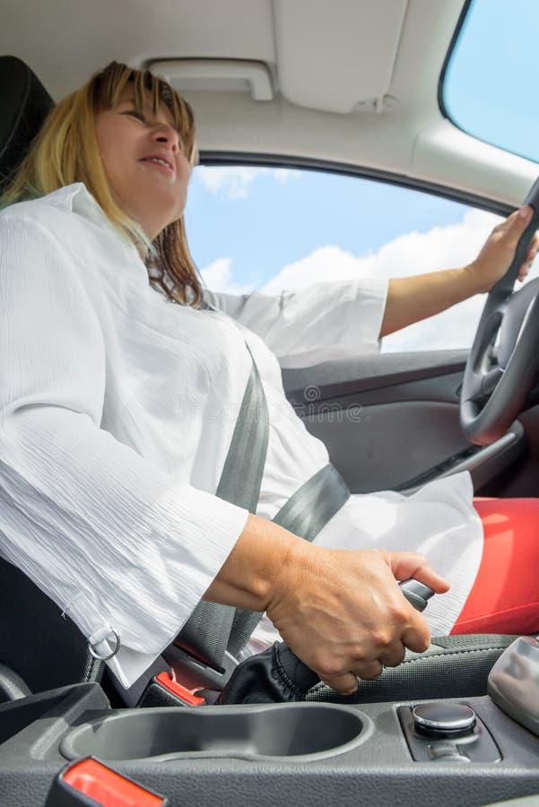 mulher em um carro que guarda o handbrake foto de stock