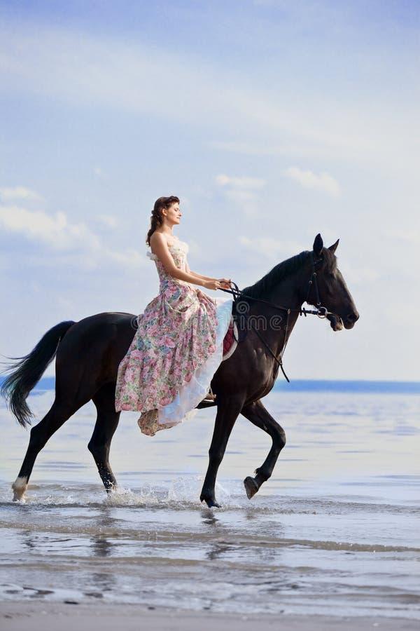 Mulher em um cavalo pelo mar imagem de stock royalty free