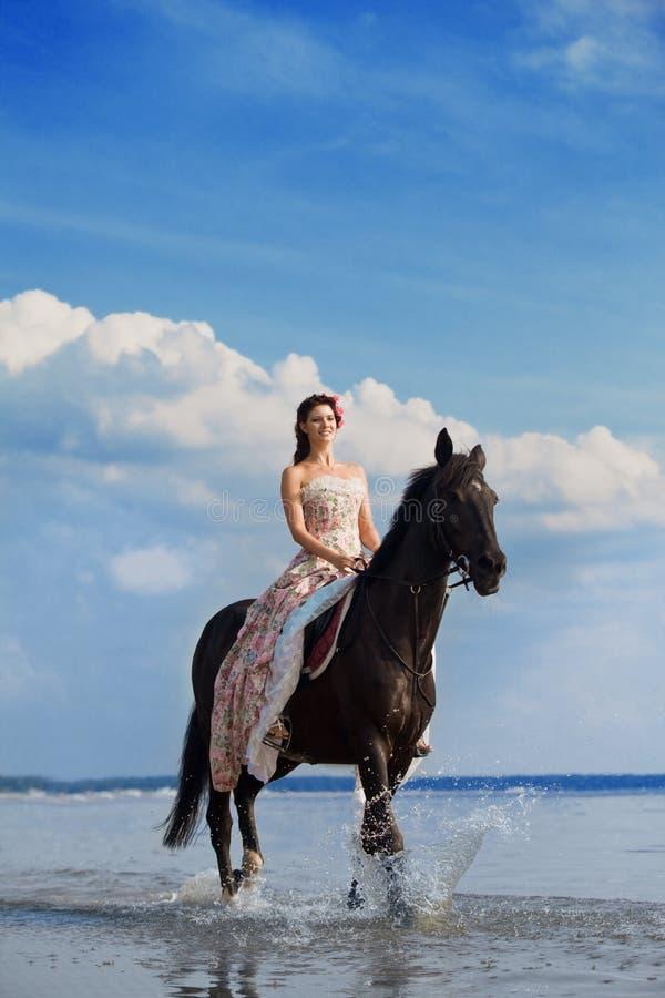 Mulher em um cavalo pelo mar imagens de stock