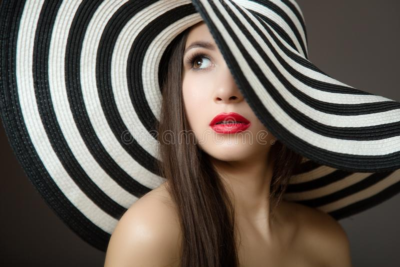Mulher em um chapéu e com bordos vermelhos Retrato de um brunette bonito novo Fundo escuro imagens de stock