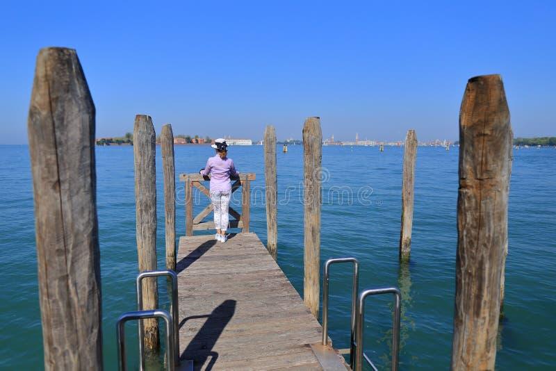 A mulher em um chapéu está de inclinação na balaustrada e olha a cidade de Veneza imagens de stock royalty free