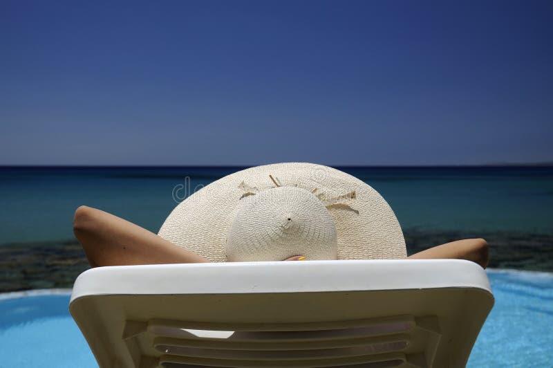 Mulher em um chapéu que descansa sobre o mar fotografia de stock royalty free