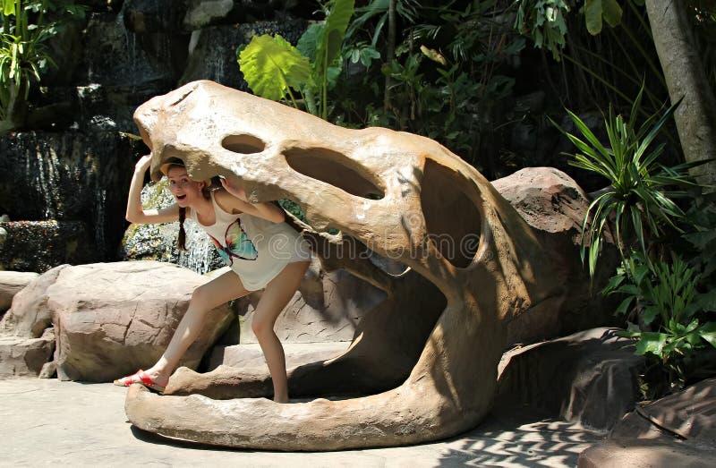 Mulher em um crânio falsificado de um dinossauro imagem de stock