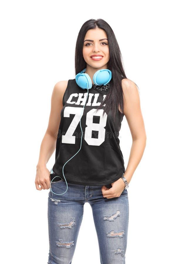 Mulher em um equipamento do hip-hop que levanta com fones de ouvido foto de stock