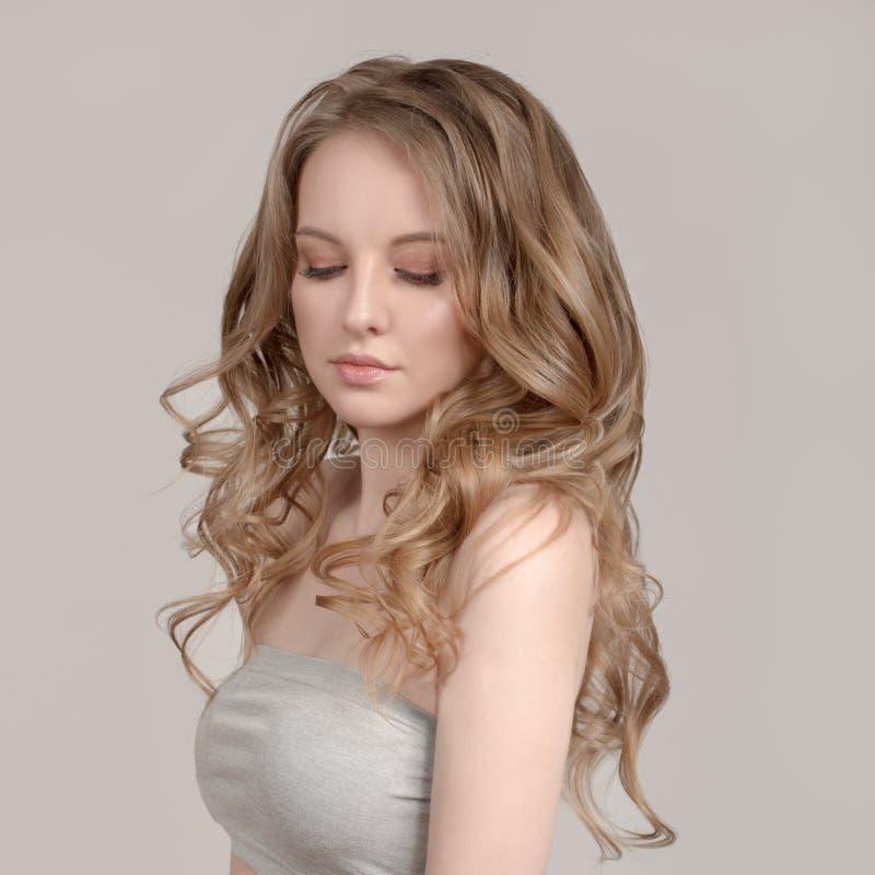 Mulher em um fundo cinzento com cabelo louro ondulado O conceito da pele limpa fotos de stock royalty free