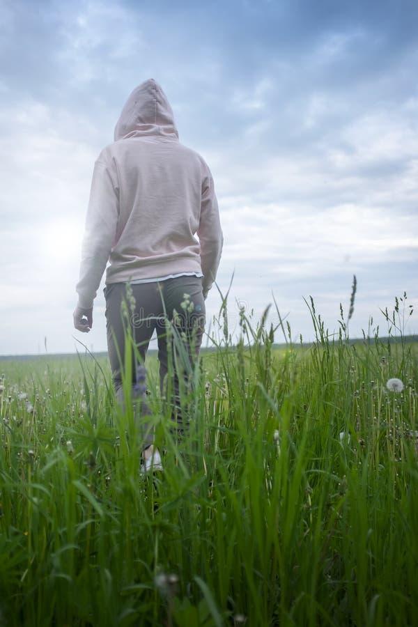 A mulher em um hoodie entra na dist?ncia no campo entre a grama para o sol fotos de stock royalty free
