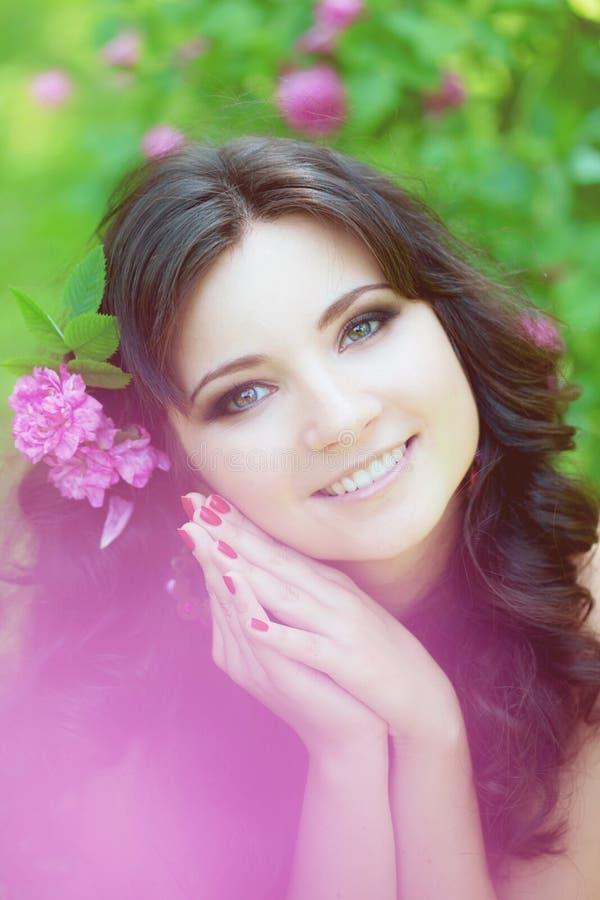 Mulher em um jardim luxúria com flores fotografia de stock
