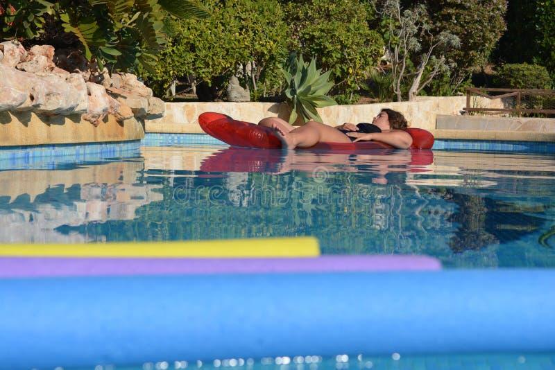 Mulher em um lilo na piscina imagens de stock