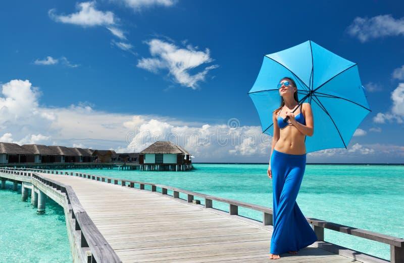 Mulher em um molhe da praia em Maldivas imagens de stock