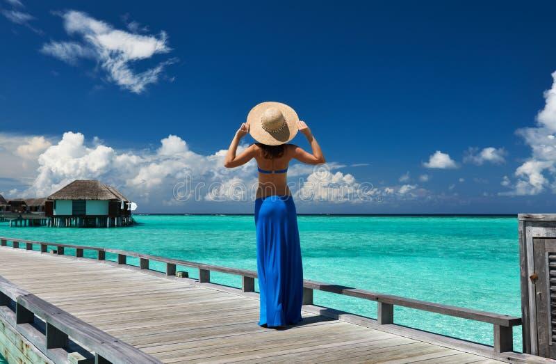 Mulher em um molhe da praia em Maldivas imagens de stock royalty free