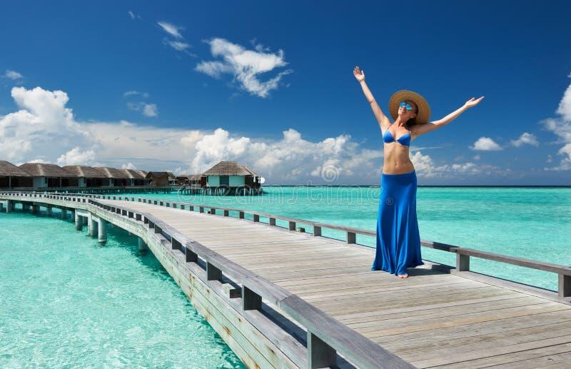 Mulher em um molhe da praia em Maldivas imagem de stock