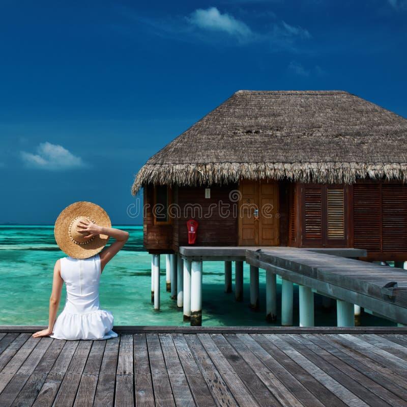 Mulher em um molhe da praia em Maldivas fotos de stock royalty free