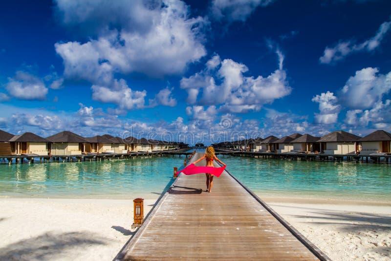 Mulher em um molhe da praia em Maldives imagem de stock royalty free