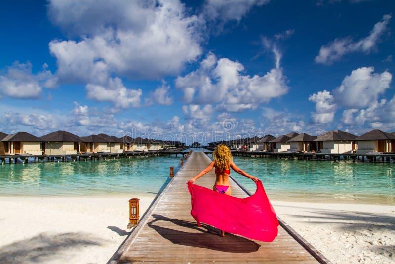 Mulher em um molhe da praia em Maldives imagem de stock