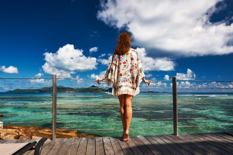 Mulher em um molhe da praia em Seychelles, La Digue fotografia de stock royalty free
