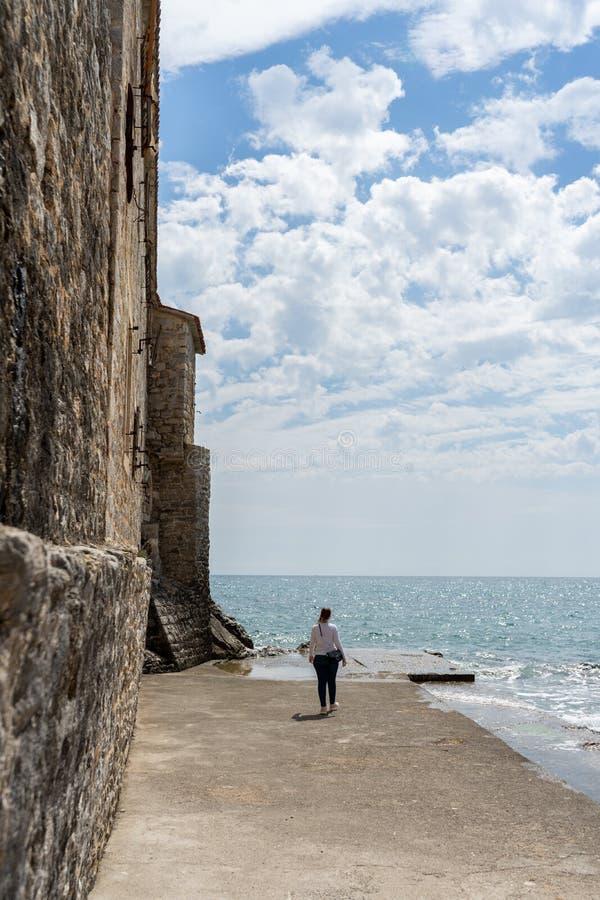 Mulher em um porto de pedra em uma cidade velha do mar de adriático Água em um cais da rocha e em uma parede medieval fora da for imagem de stock