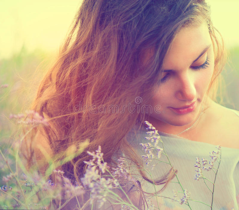 Mulher em um prado com Violet Flowers foto de stock royalty free